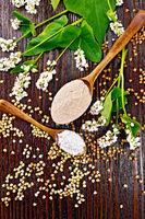 Flour buckwheat brown and green in spoons on dark board top