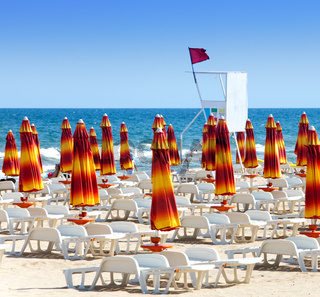 The closed beach umbrellas and red flag -swimming  is forbidden