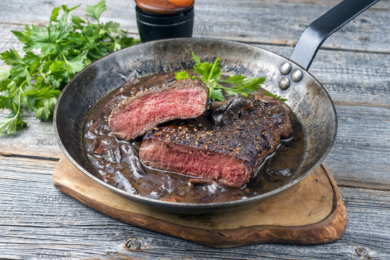 Traditional dry aged fried loin of a horse steak natural with mushroom and onions in a red wine jus served as close-up in a rustic frying on a wooden board