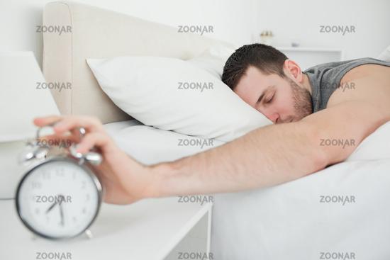 Sleeping handsome man being awakened by an alarm clock