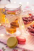 Sweet French macarons in cookie box with candles in vintage style
