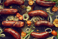 Top view on delicious grilled sausages served with onion, tomatoes, garlic, bread and herbs