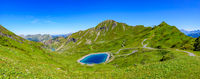 Panoramic landscape of mountains of Alps in summer with flowers and a lake in Portes du Soleil, France, Europe