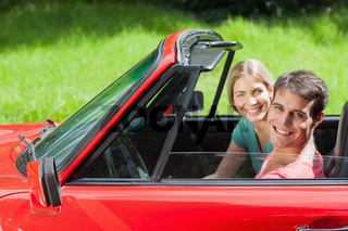 Cheerful young couple having a ride in red cabriolet