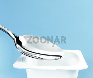 Yogurt cup and silver spoon on blue background, white plastic container, fresh dairy product for healthy diet and nutrition