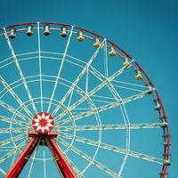 Ferris wheel attraction on blue sky background.