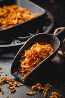 Homemade fried onions in iron kitchen scoop with black pan on black background