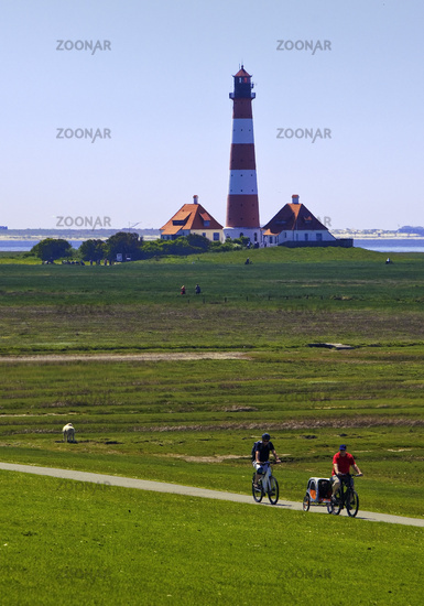 Westerhever lighthouse with cyclists, Wadden Sea National Park, North Frisia, Germany, Europe