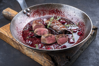 Traditional wild hare back filet braised with wild berries and cherry relish souse served as close-up in rustic frying pan on an old wooden board