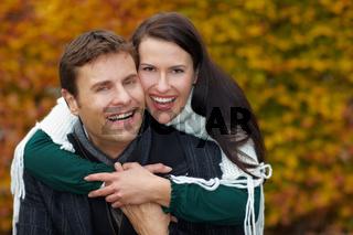 Mann trägt Frau huckepack in der Natur