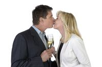 Mann und Frau küssen sich und feiern mit Sekt