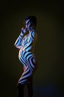 Naked pregnant woman in studio with stripes shadows body paint