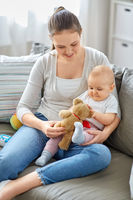 mother with baby playing with teddy bear at home