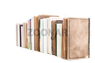 Assortment of new and old books in a row isolated on white background.