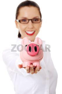 Happy business woman with her savings in a piggy bank