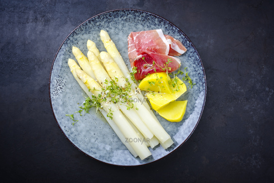 Traditional steamed white asparagus with cured ham and boiled potatoes garnished with butter sauce served as top view on a Nordic design plate with copy space