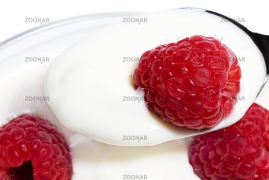 closeup of a raspberry on a spoon with yogurt