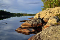 Northern Karelia, Russia. Rocky shore of Lake Pongoma on a sunny summer evening,