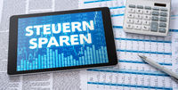 A tablet with financial documents - Save taxes in german - Steuern sparen