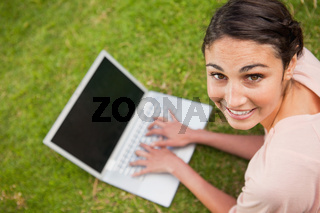 Woman looking to her side while using a laptop