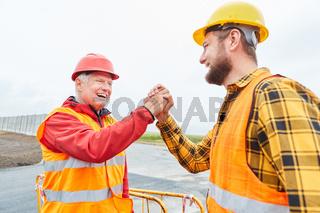 Architekt und Bauarbeiter begrüßen sich mit Handschlag