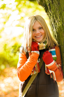 Happy blonde teenager girl autumn forest smiling