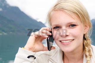 junge blonde Frau telefoniert mit ihrem Smartphone