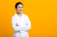Portrait of indian doctor woman in white medical gown isolated on yellow background