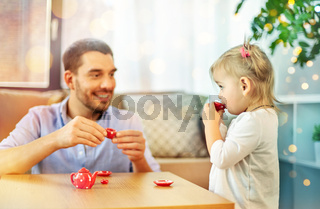 father and daughter playing tea party at home