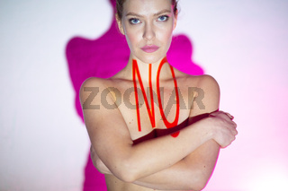 Young adult woman with word NO on her body