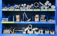 pipes, metal pieces and various metal parts for a CNC machine standing on a shelf