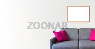 Empty wooden picture frame on a white wall above a sofa. Horizontal banner