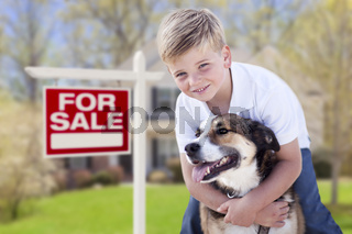 Young Boy and His Dog in Front of For Sale Sign and House