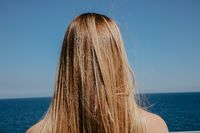 Back of blonde long-haired young woman watching blue sea horizont.