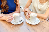close up of young women with coffee cups at cafe