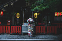 Woman in traditional kimono praying at Nonomiya Shrine in the evening in Kyoto, Japan
