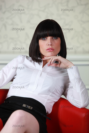Smart businesswoman alone in armchair