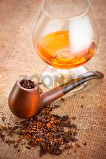 Glass of cognac and pipe with tobacco