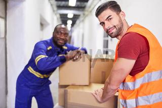 Zwei Lagerarbeiter transportieren Pakete