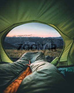 person sitting in the tent with cup looking at the mountain landscape. View from inside