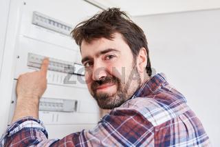 Elektriker kontrolliert Sicherung im Verteilerkasten