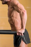 Close up of a Muscular man doing triceps dip on parallel bars in gym.
