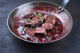 Traditional wild hare back filet braised with wild berries and cherry relish souse served as close-up in rustic frying pan on a black board