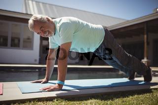 Smiling senior man doing push-up near swimming pool