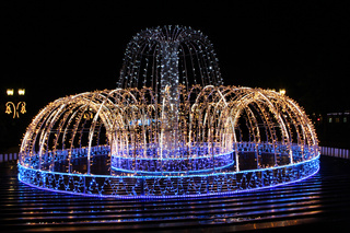 Beautiful blue lights in New Year holidays in night. Bright fountain in darkness