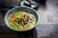 German liver dumpling soup with onion and vegetable on dark background
