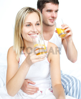 Lovers drinking orange juice in bed