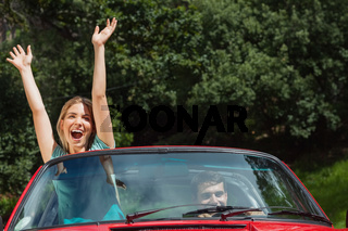 Happy couple having fun in their red cabriolet