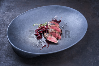Modern style traditional wild hare back filet braised with wild berries and cherry relish souse served as close-up on Nordic design plate with copy space