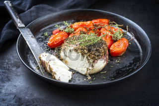 Traditional Italian Ricotta al forno cake with barbecue tomatoes and herbs offered as close-up on a rustic plate